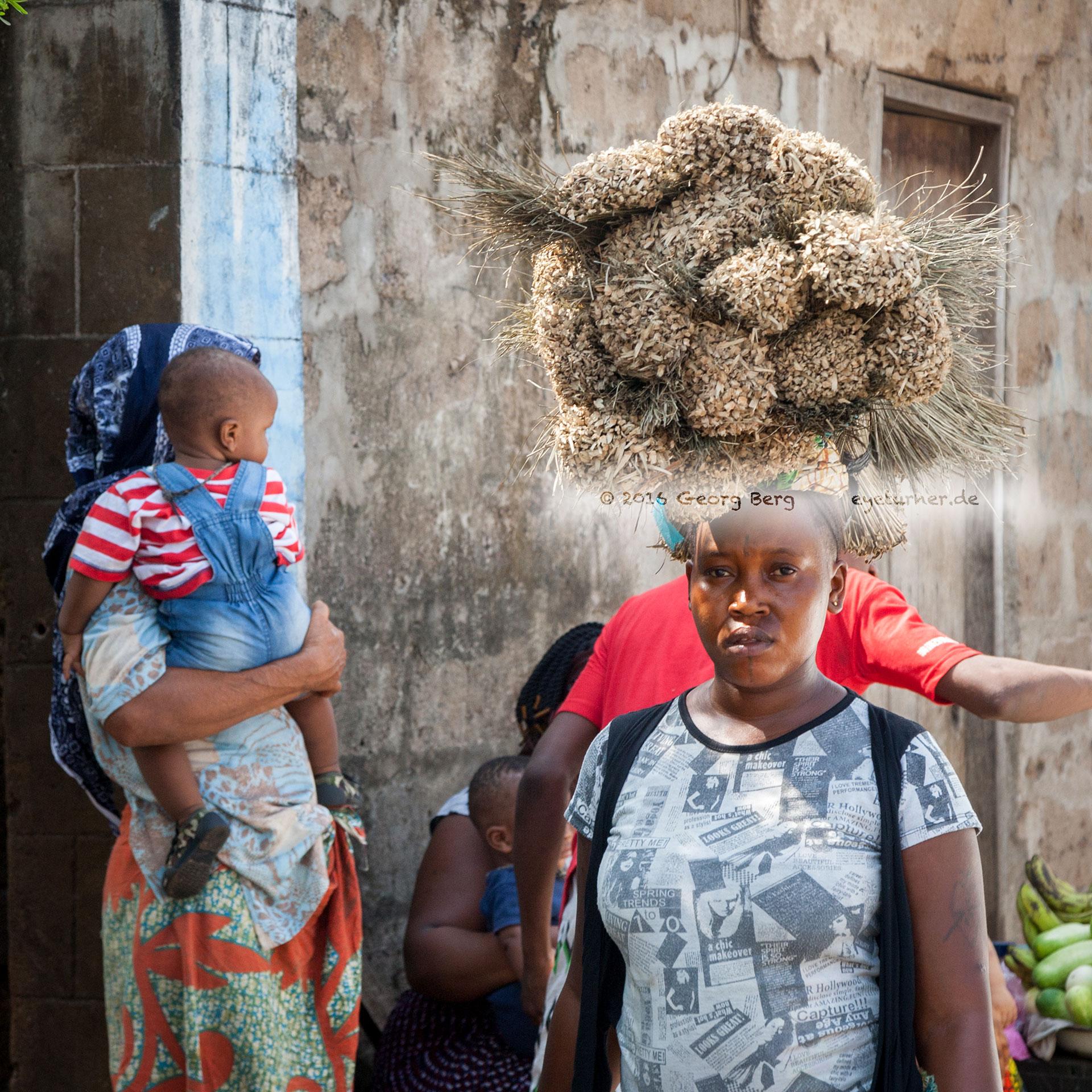 Frau aus Sierra Leone mit Bürsten auf dem Kopf